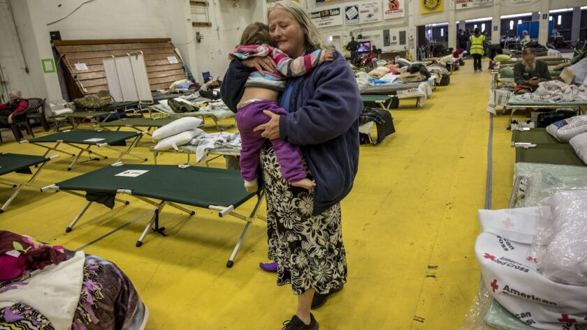 Dawn Heaton, 51, comforts her grand daughter Ariel Norton, 13 months, in the Red Cross shelter where evacuees from the Camp Fire can live inside a heated building at the Butte County Fairgrounds on Sunday, Nov. 18, 2018 in Gridley, Calif.