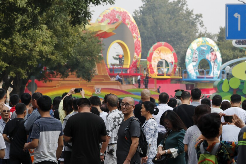 Residents watch a float behind barricade line as Chinese military vehicles and floats in preparation for the parade for the 70th anniversary of the founding of the People's Republic of China, in Beijing, Tuesday, Oct. 1, 2019. Tuesday's event marks the anniversary of the Oct. 1, 1949, announcement of the founding of the People's Republic of China by then-leader Mao Zedong following a civil war. (AP Photo/Andy Wong)