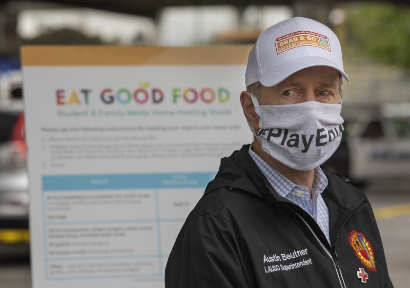 "Austin Beutner wears a face mask and stands next to an ""Eat Good Food"" sign."