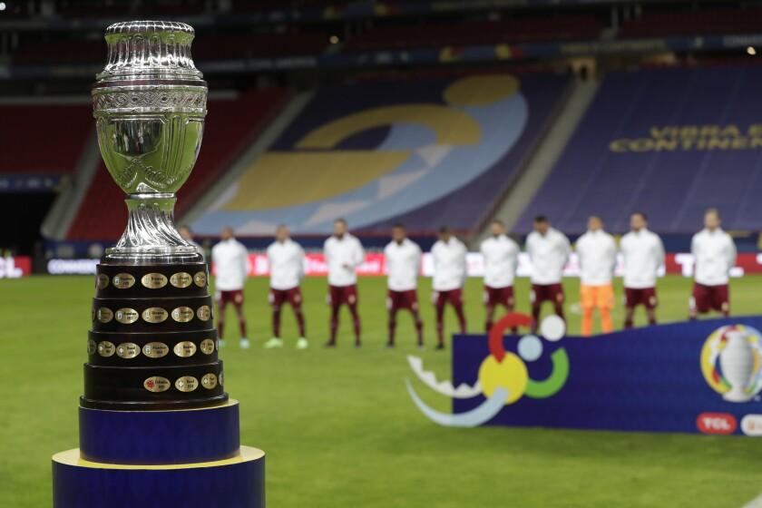 La foto del domingo 13 de junio de 2021 muestra el trofeo de la Copa América, delante de los jugadores de Venezuela.