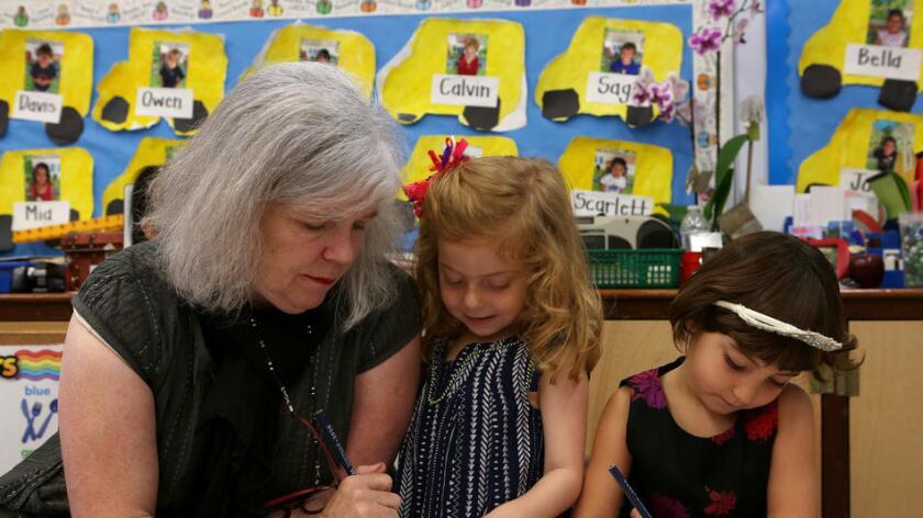 Missy Morris ayuda a los estudiantes Emma Jean de Souza y Jesse Rhoden en el salón de clases. (Katie Falkenberg/Los Angeles Times)