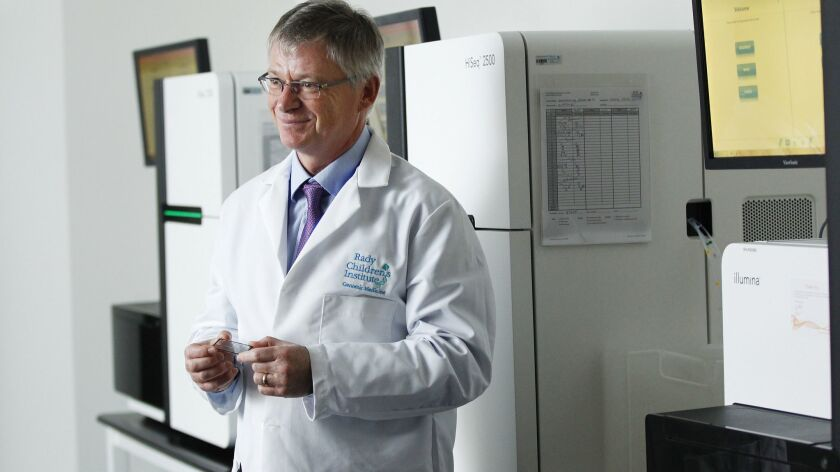 Dr. Stephen Kingsmore, President and CEO of Rady Children's Institute for Genomic Medicine, stands in a lab with three Illumina sequencing machines at the Institute.