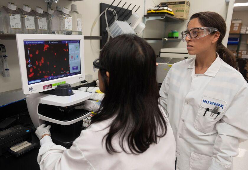 Dr. Sonia Macieiewski and Dr. Nita Patel look at a sample of a respiratory virus at Novavax labs