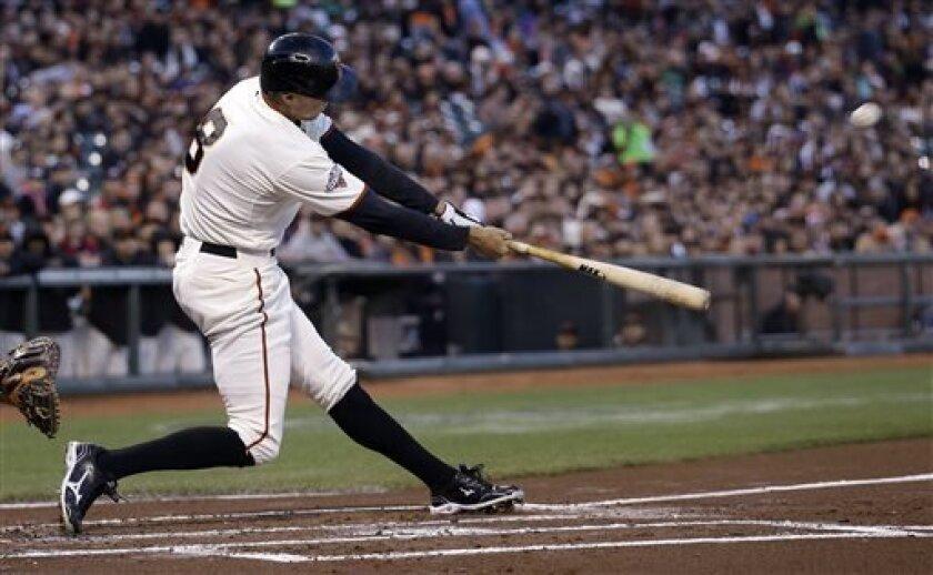 San Francisco Giants' Hunter Pence (8) hits a three-run home run off of Colorado Rockies pitcher Jorge De La Rosa (29) during the first inning of a baseball game in San Francisco, Monday, April 8, 2013. (AP Photo/Jeff Chiu)