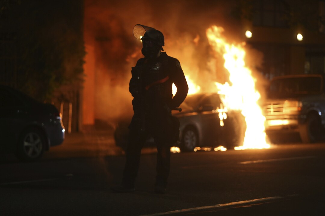 A police officer is silhouetted near a burning car.