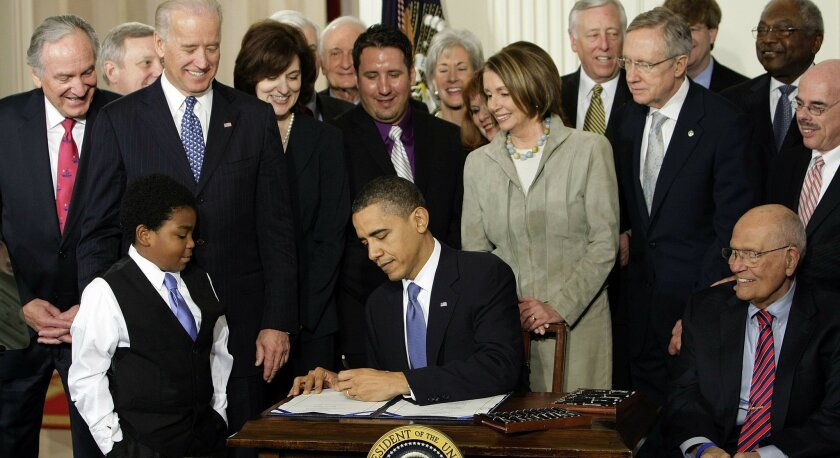 """FILE - In this March 23, 2010 file photo, President Barack Obama signs the health care bill in the East Room of the White House in Washington. With the nation still divided over """"Obamacare,"""" President Barack Obama is laying out a blueprint for addressing unsolved problems with his signature health"""