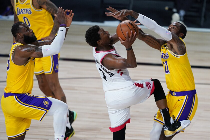 Lakers' LeBron James, left, and JR Smith, right, guard Toronto Raptors' Kyle Lowry during the second half on Saturday.