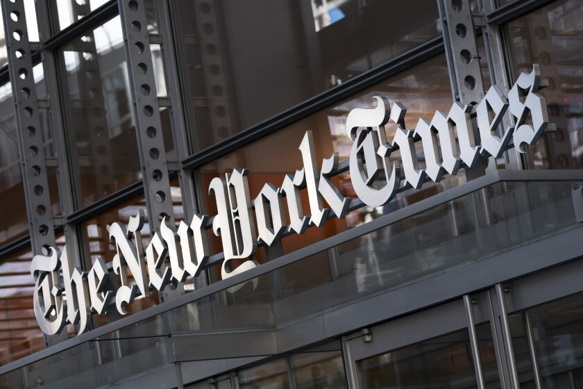 FILE - In this Thursday, May 6, 2021 file photo, a sign for The New York Times hangs above the entrance to its building