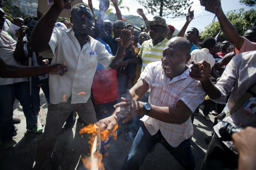 A man yells out in pain as his hand catches fire from a burning Dominican national flag he was holding, during an anti-Dominican Republic protest, in front of the country's consulate in Port-au-Prince, Haiti, Wednesday, Feb. 25, 2015. Protesters outraged over a Feb. 11 lynching of young man of Haitian descent in the Dominican city of Santiago are demanding that the neighboring country respect the human rights of Haitians. (AP Photo/Dieu Nalio Chery)