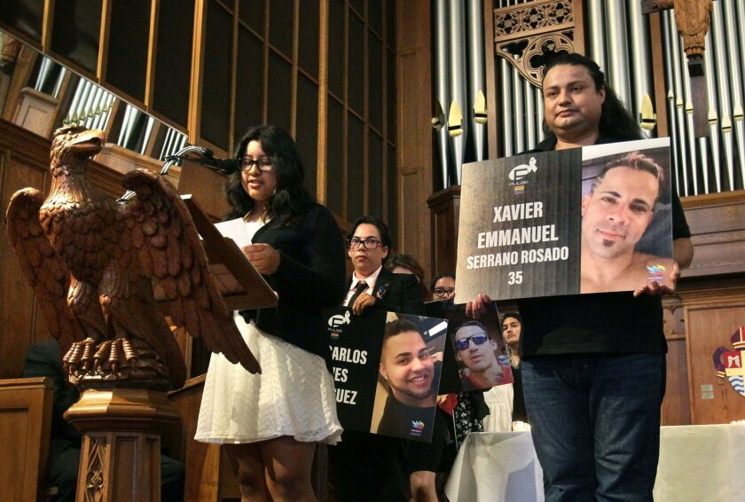 Grace Otero reads the name of 35 year old Xavier Emmanuel Serrano Rosado, one of the 49 Orlando, Florida shooting victims as his portrait is held by Roy Castillo during the San Diego Latino/Latina/Latinx Memorial for Orlando at St. Paul's Episcopal Cathedral.