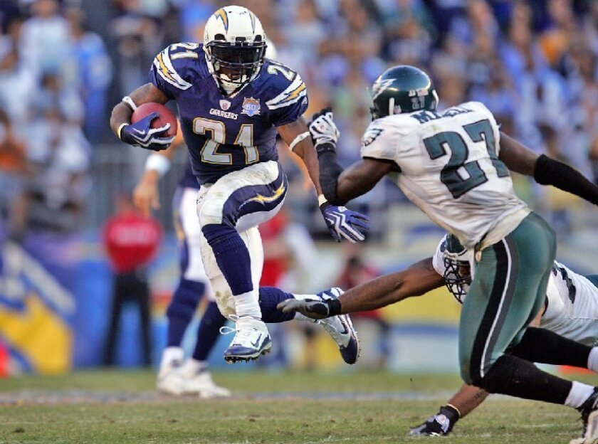 The Chargers' LaDainian Tomlinson, who scored twice, leaps past Eagles defenders on the team's final drive in the fourth quarter.