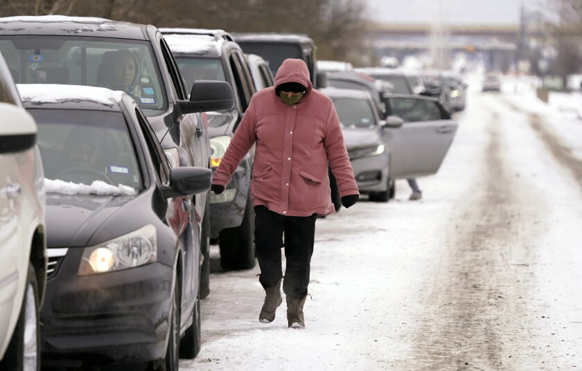 People line up in cars on a snow-covered road while a pedestrian in a coat walks next to them.