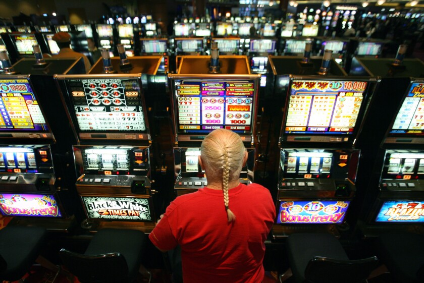 A gambler puts money into a slot machine at casino in Riverside County, one of four counties that were audited.