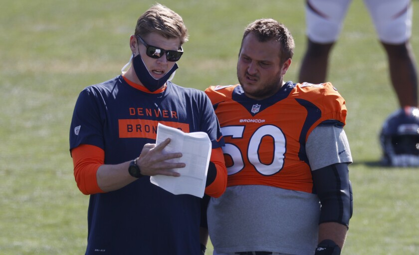 Denver Broncos assistant offensive line coach Chris Kuper, left, confers with center Patrick Morris as he takes part in drills during an NFL football camp practice Monday, Aug. 17, 2020, in Englewood, Colo. (AP Photo/David Zalubowski)