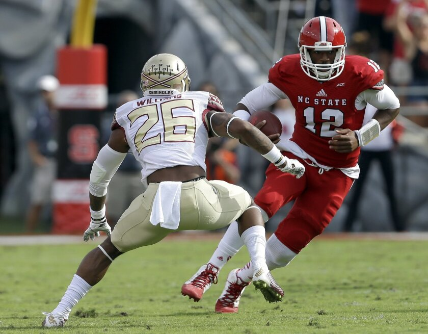 Florida State's P.J. Williams (26) looks to tackle North Carolina State quarterback Jacoby Brissett (12) during the first half of an NCAA college football game in Raleigh, N.C., Saturday, Sept. 27, 2014. (AP Photo/Gerry Broome)