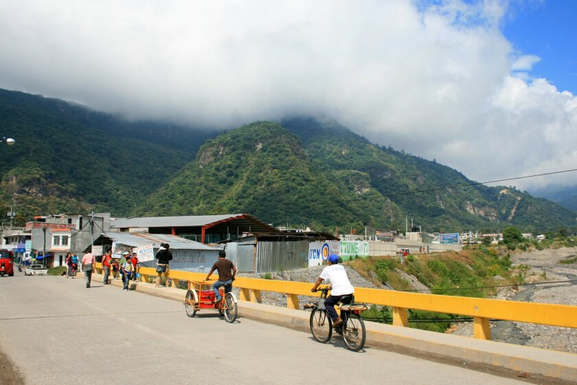 In this Dec. 2015 photo, people ride bikes on the road to Panajachel, Guatemala. The walk between Santa Catarina Palopo and Panajachel offers views of the lake, volcanoes and everyday village life. (Kristi Eaton via AP)