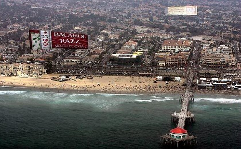 """An aerial advertisement is pulled high above Huntington Beach Pier. A debate over the banners in Hermosa Beach has resulted in a """"code of conduct"""" for pilots that will be tested at this weekend's International Surf Festival. More photos >>>"""