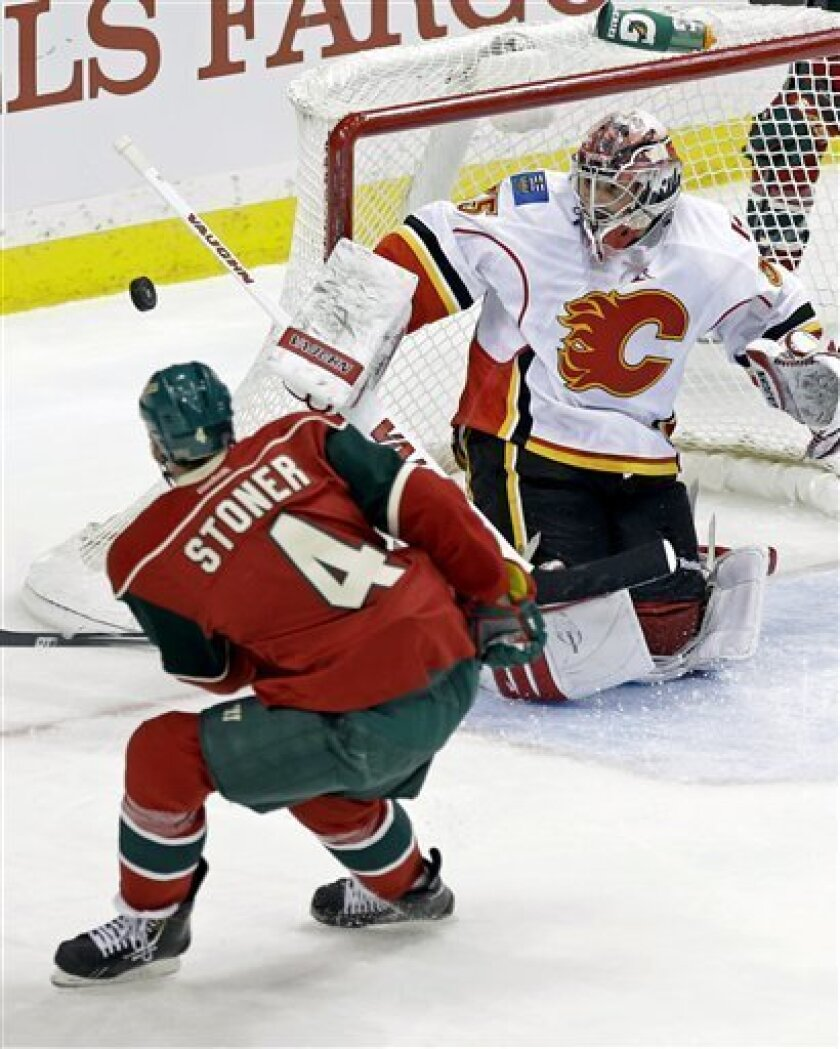 Calgary Flames goalie Joey MacDonald stops a shot on goal by Minnesota Wild's Clayton Stoner in the first period of an NHL hockey game Tuesday, Feb. 26, 2013, in St. Paul, Minn. (AP Photo/Jim Mone)