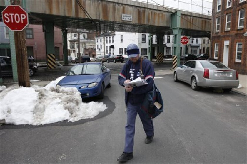 Letter carrier Kevin Pownall delivers mail in Philadelphia, Tuesday, March 2, 2010. The U.S. Postal Service is increasing the pressure for dropping Saturday home delivery as it seeks to fend off massive financial losses. (AP Photo/Matt Rourke)