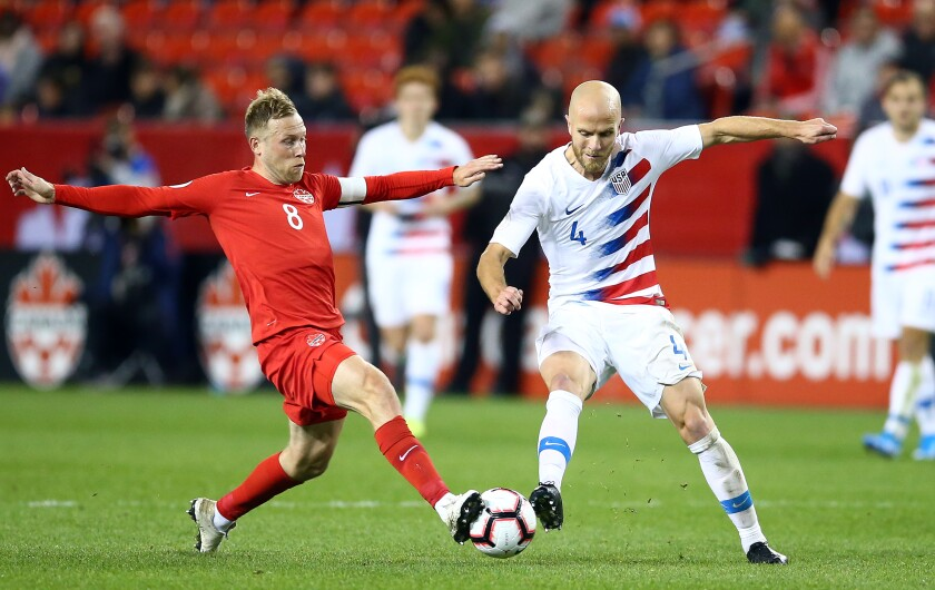 U.S. midfielder Michael Bradley (4) battles for the ball against Canada's Scott Arfield during a CONCACAF Nations League game on Oct. 15, 2019, in Toronto.