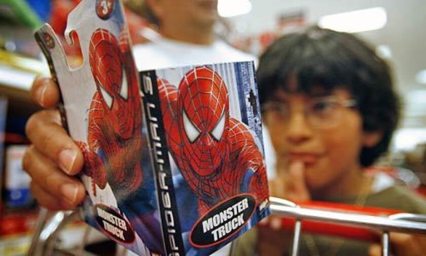 """Gabriel Reynoso, 7, picked out a Spider-Man monster truck toy while shopping with his dad, Juan Reynoso (rear) and baby brother at Target. """"Spider-Man 3,"""" """"Pirates of the Caribbean: At World's End"""" and """"Transformers"""" all have toys modeled after the characters."""