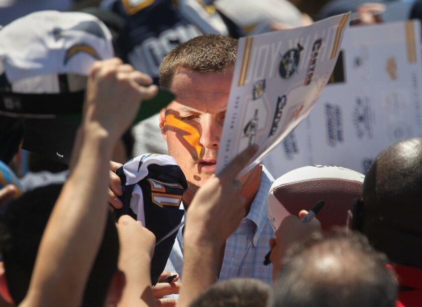 In this April file photo, Chargers quarterback Philip Rivers signs autographs as a fan's reflected bolt flashes across his face after the team finished a signature-gathering rally for its stadium ballot initiative.