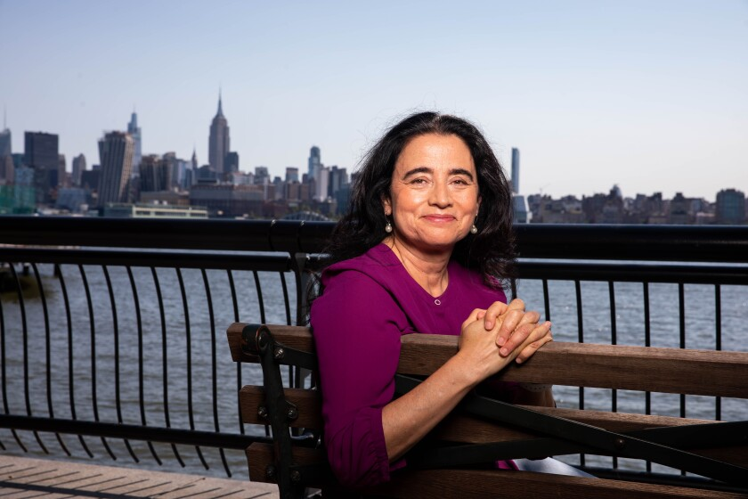 """Patricia Cardoso, director of """"Real Women Have Curves,"""" sits on a bench in front of a city skyline."""