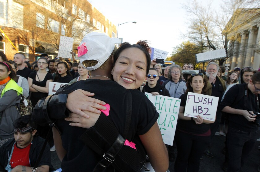 Protester Mitch Xia, facing the camera, gets a hug from Zakyree Wallace during a March protest in Chapel Hill, N.C., over state legislation reversing a Charlotte ordinance extending some rights to people who are transgender or gay.