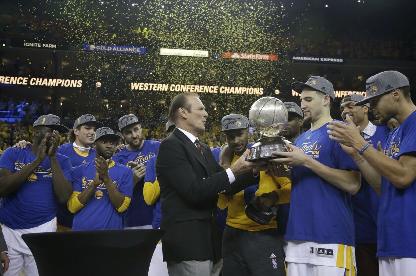 Former NBA player Rick Barry, center, presents the Western Conference finals trophy to Golden State Warriors guard Klay Thompson, second from right, after the Warriors beat the Oklahoma City Thunder in Game 7 of the NBA basketball Western Conference finals in Oakland, Calif., Monday, May 30, 2016.