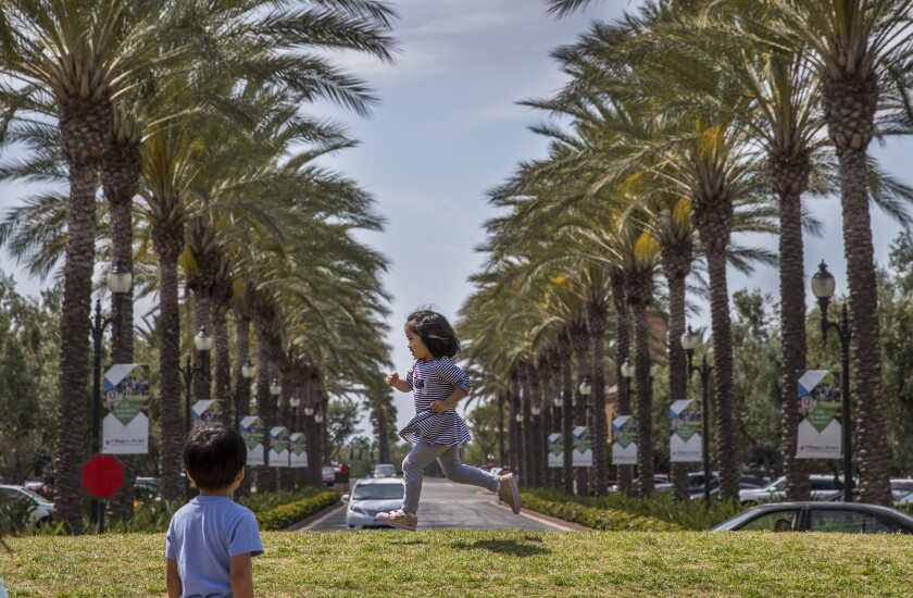 Kate Claribel, 3, whose parents just bought a home in Irvine, plays with other kids in the grass alo