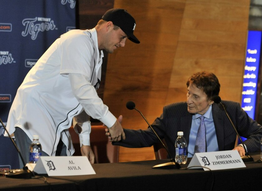 FILE - In this Nov. 30, 2015, file photo, Detroit Tigers pitcher Jordan Zimmermann shakes hands with Tigers owner Mike Ilitch, right, during the news conference in Detroit. An offseason of big spending may put the Detroit Tigers back in contention after a last-place finish in 2015. (Robin Buckson/D