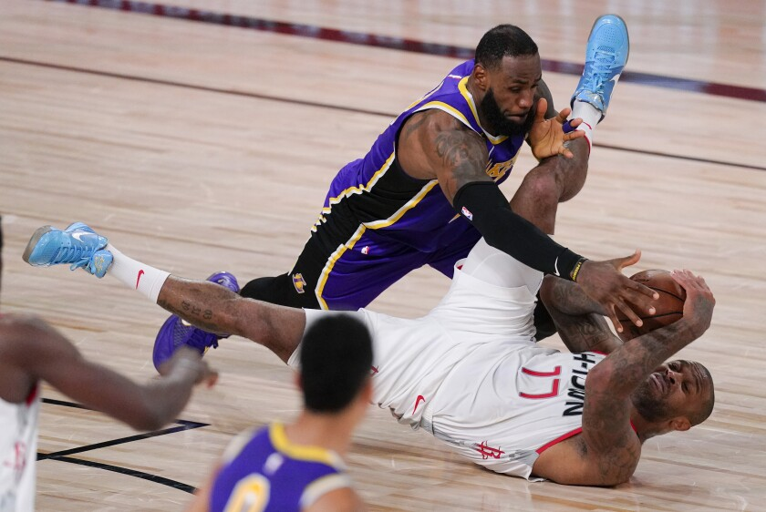 Rockets forward P.J. Tucker (17) is fouled by Lakers forward LeBron Jame during Game 1.