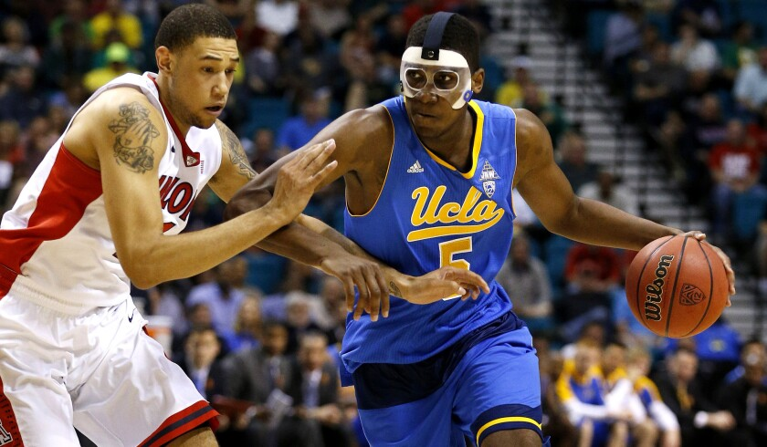 UCLA forward Kevon Looney drives past Arizona forward Brandon Ashley in the first half of the Pac-12 semifinal game Friday.