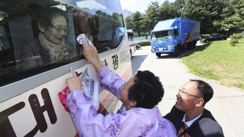 North Korean Kim Kyong Sil, 72, center, touches the bus window in her attempt to feel hand of her So