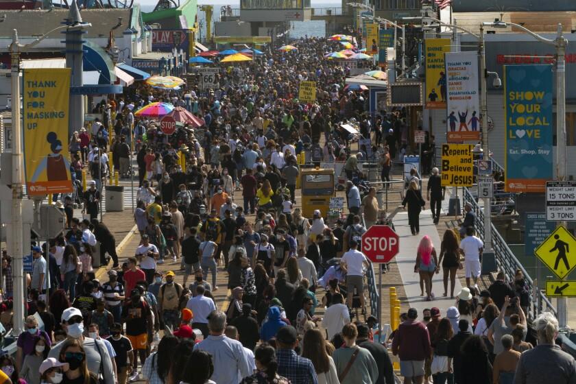 People crowd the Santa Monica Pier in Santa Monica, Calif., Saturday, May 29, 2021.