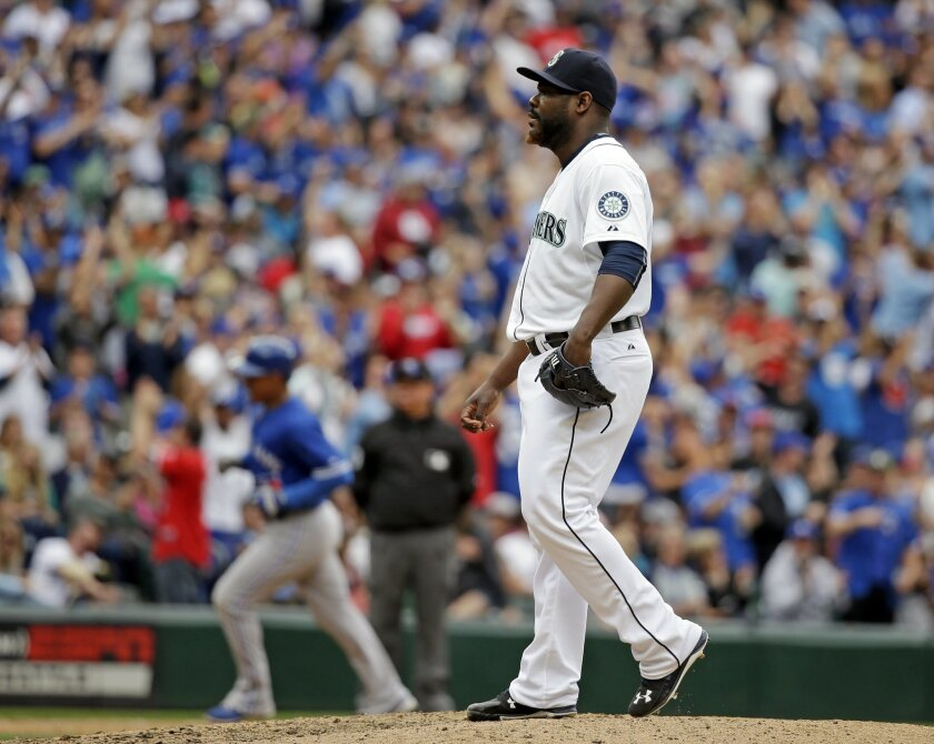Seattle Mariners relief pitcher Fernando Rodney, right, waits on the mound as Toronto Blue Jays' Ezequiel Carrera rounds the bases after hitting a two-run home run in the eighth inning of a baseball game Saturday, July 25, 2015, in Seattle. (AP Photo/Elaine Thompson)