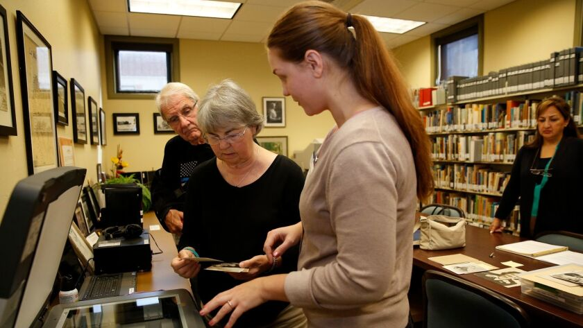 Library assistant Dana Sneberger gives Debbie Hill-Williams (center) and her husband, Bob Williams, hands-on instruction at the new Memory Lab at the La Jolla-Riford Library. Patrons can use software to convert their VHS tapes, photos and other keepsakes to a digital format.