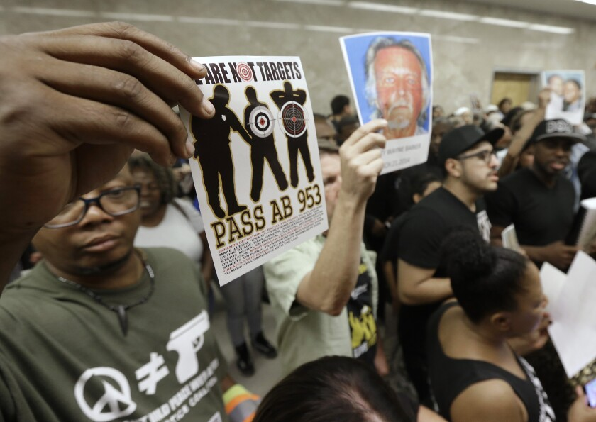 """FILE - In this Sept. 2, 2015 file photo protestors shouting """"black lives matter"""" hold up photos of people they claim are the victims of police violence as they block the hallway outside the governors office while successfully demanding the passage of AB953, in Sacramento, Calif. Black drivers in California were stopped by police at 2.5 times the per capita rate of whites and searched three times as often, according to the latest report Thursday, Jan. 2, 2020, from a first-in-the-nation attempt to track racial profiling by police. (AP Photo/Rich Pedroncelli, File)"""