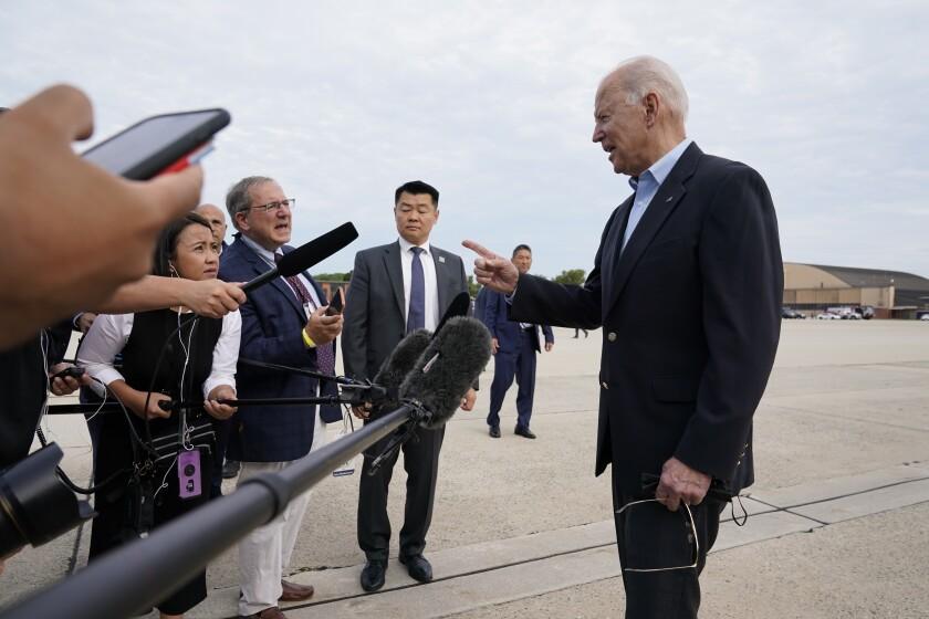 President Biden talks to a line of reporters on tarmac.