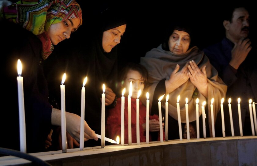 Pakistani women light candles during a vigil for victims of the Bacha Khan University attack, Wednesday, Jan. 20, 2016 in Peshawar, Pakistan. Taliban gunmen stormed a university in northwestern Pakistan on Wednesday, killing many people and triggering an hours-long gun battle with the army and police before the military declared that the assault in a town near the city of Peshawar was over. (AP Photo/Mohammad Sajjad)