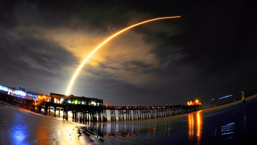A SpaceX Falcon 9 rocket streaks over the Cocoa Beach Pier in Florida after its liftoff from Cape Canaveral early Sunday.