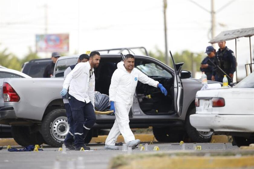 Personal médico forense trabajas en el sitio donde un grupo armado se enfrentó con la policía, en el municipio de Tlajomulco, estado de Jalisco, occidente de México, con saldo preliminar de 5 muertos y dos heridos. EFE/Archivo