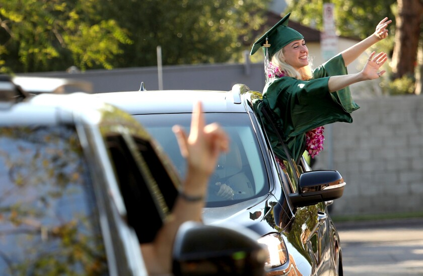 A high school graduate in green cap and gown waves to her teachers through the open window of a car