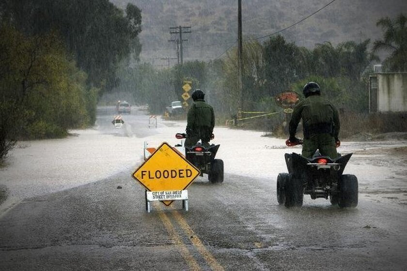 Two Border Patrol agents uses all-terrain vehicle to get through the flooded Hollister Road in south San Diego. (Nelvin C. Cepeda/Union-Tribune)