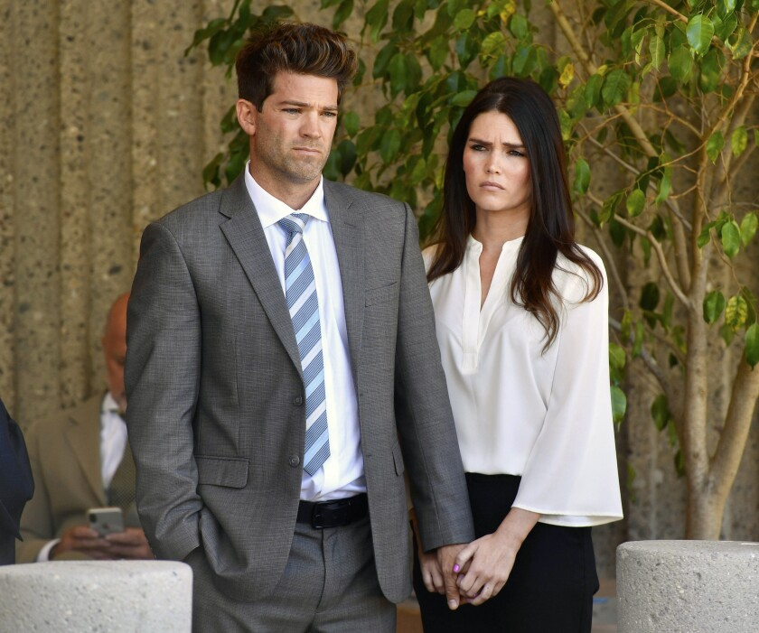 FILE - In this Oct. 17, 2018, file photo, Dr. Grant Robicheaux and his girlfriend Cerissa Riley listen during a news conference by their lawyer Philip Kent Cohen in Newport Beach, Calif. State prosecutors want to drop most sex crime charges filed against a reality TV doctor and his girlfriend, who are accused of drugging and raping several women at their Southern California home. The attorney general's office, which took over the case last year, asked an Orange County judge on Friday, May 14, 2021, to drop charges involving six of seven alleged victims. (Paul Bersebach/The Orange County Register via AP, File)