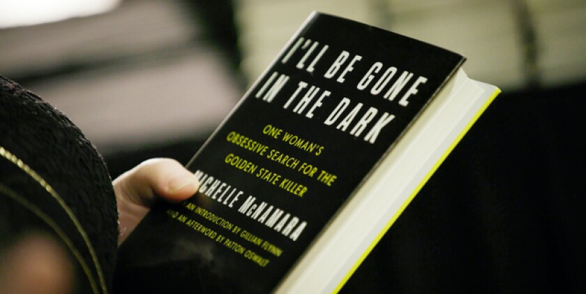 """A hand holding a copy of Michelle McNamara's book """"I'll Be Gone In The Dark"""""""