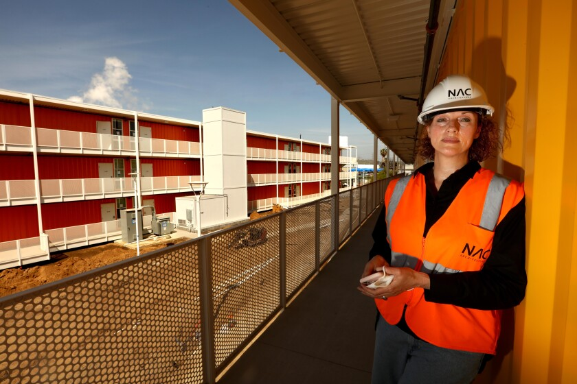 Architect Louise Griffin, in hard hat and safety vest, stands on the outdoor terrace of a shipping container tower
