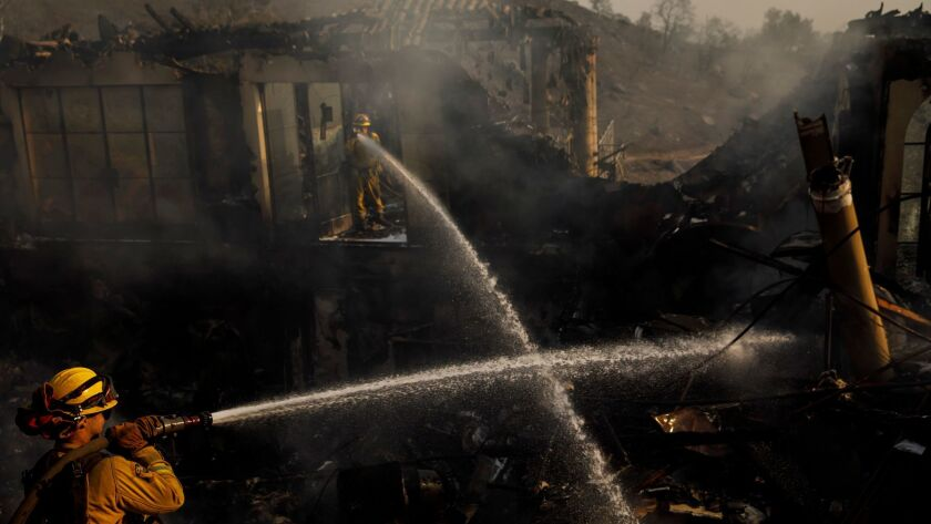 Humboldt County firefighters Lonnie Risling, left, and Jimmy McHaffie spray down smoldering fire beneath the rubble of a home that was destroyed by the Thomas fire in Montecito on Sunday.
