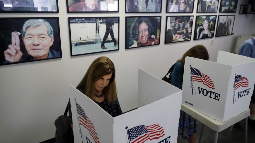 Voters fill out their ballots at the Los Angeles County Registrar of Voters office Tuesday, Oct. 23,