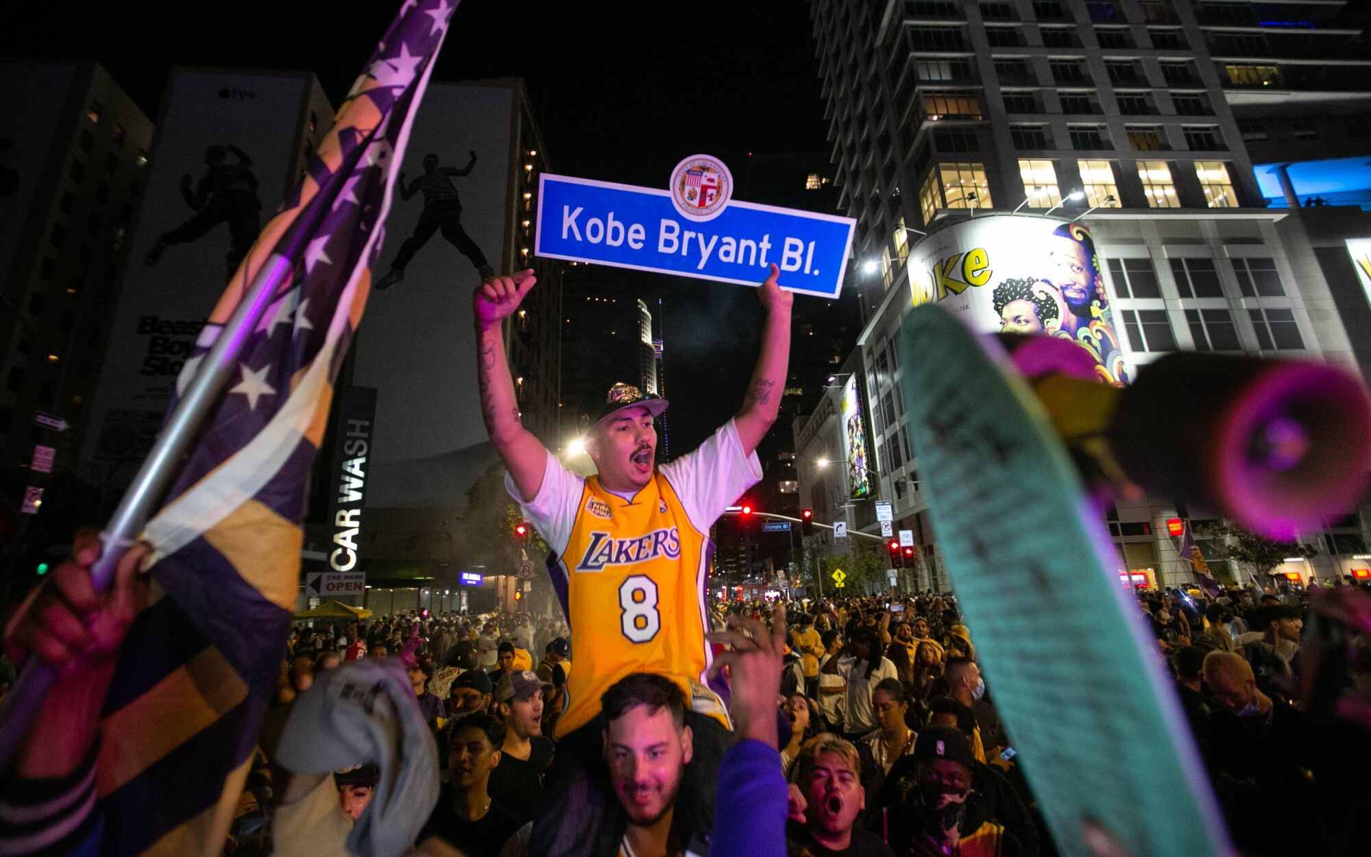 A man in a gold Lakers 8 jersey on the shoulders of another man holds a Kobe Bryant Boulevard street sign